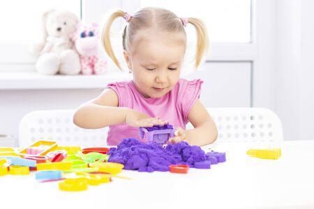 Photo for Girl plays kinetic sand in quarantine. Blond beautiful girl smiles and plays with purple sand on a white table. - Royalty Free Image