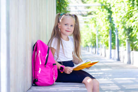 Photo pour schoolgirl sits on a bench in the street with a backpack and reads a textbook, book. Back to school. A cute schoolgirl with long ponytails. - image libre de droit