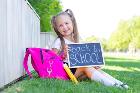 Photo pour schoolgirl sits on the grass, school backpack. Holds a sign in his hands with the inscription back to school - image libre de droit