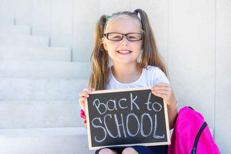 Photo pour schoolgirl with glasses sits on the stairs, school backpack. Holds a sign in his hands with the inscription back to school - image libre de droit