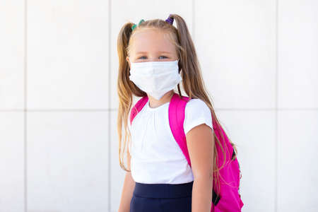 Foto de schoolgirl stands with a backpack in a protective medical mask - Imagen libre de derechos