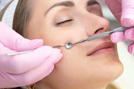 Photo pour Procedure for cleaning the skin of the face with a steel appliance with a spoon from blackheads and acne. - image libre de droit