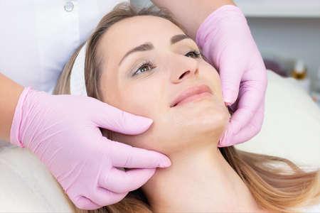 Photo pour Cosmetological facial massage. beautician doing facial massage to a satisfied beautiful young woman - image libre de droit