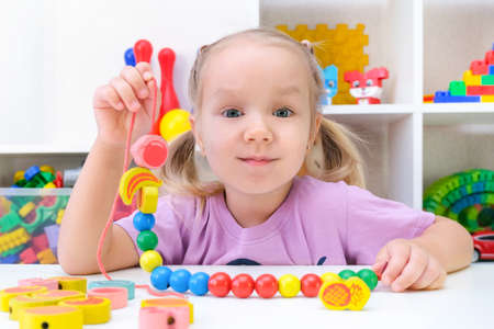 Foto de speech therapy, the development of fine motor skills. Toddler girl is stringing beads on a string. - Imagen libre de derechos