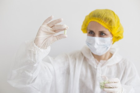 Scientist in white protective suit holding pill. Close up photo