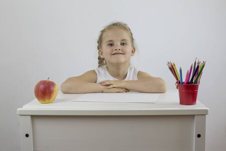 A contented little girl is sitting at her desk with pencils and a ripe apple