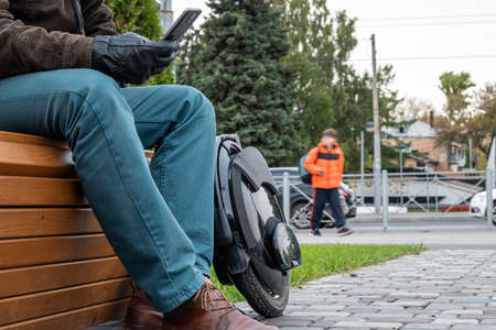Photo for Electric monowheel, innovative personal vehicle, electric unicycle, ecological urban transport of the future. A man with a smartphone on a Park bench. Black leather gloves, jeans, and brown shoes - Royalty Free Image