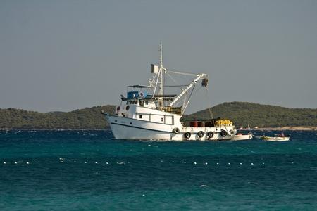 Aquamarine, white and green presenting white fishing boat