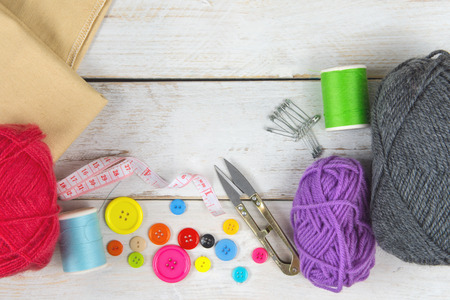 Foto per Sewing and crafting Includes thread, yarn, button, scissors, measuring tape and brooch. Placed on a white vintage wooden floor. - Immagine Royalty Free