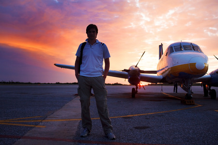 Young man on the runway in background of a small private plane