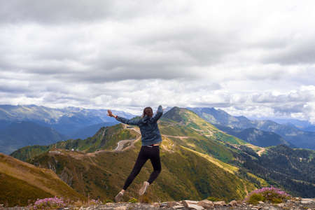 Photo pour A young female tourist on top of a mountain jumps into the sky. Happiness and a sense of freedom, travel in the mountains, the power of nature - image libre de droit