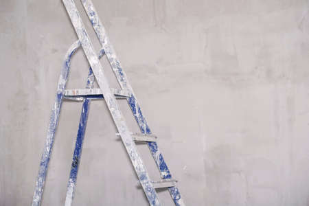 Single blue dirty aluminum folding metal step ladder leaning against gray plaster wall background
