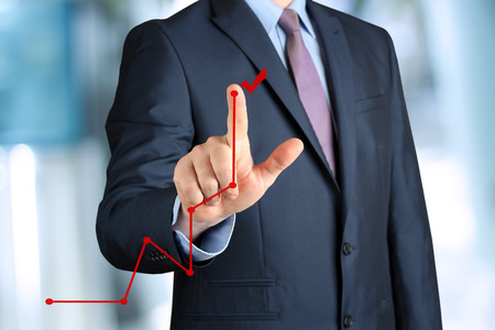 Bisinessman  ?? a modern suit Touching   a Graph by hand. Green background beside