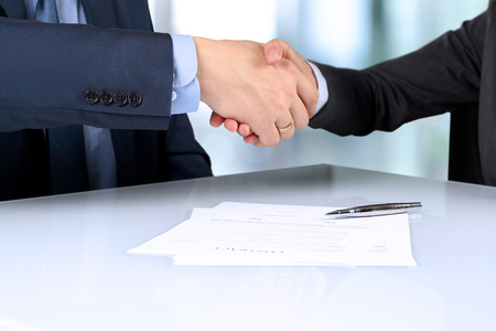 Close-up image of a firm handshake between two colleagues after signing a conntract