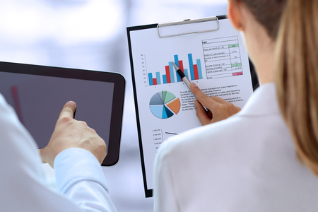 Photo pour Business colleagues working and analyzing financial figures on a graphs - image libre de droit
