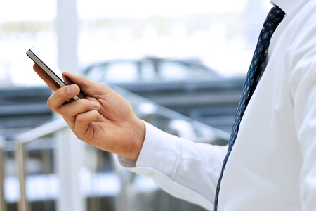 Cropped view of Businessman holding the mobile  phone standing in front the window