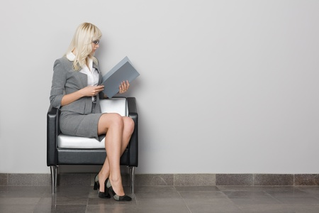 Photo for Attractive young business woman sitting in a chair. Waiting room. - Royalty Free Image