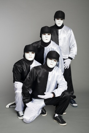 Portrait of a team of young break dancers in stylish uniforms on a gray background.