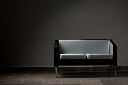 Modern lounge couch against a gray wall. Studio lighting.