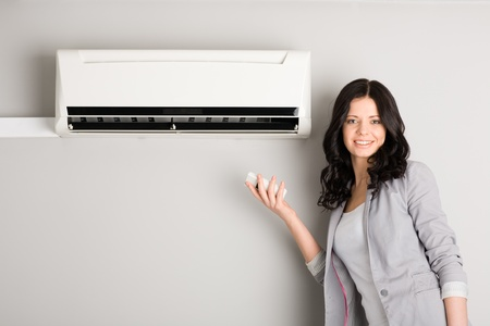 Beautiful girl holding a remote control near the air conditioner