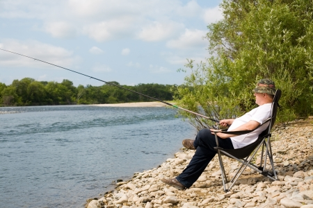 Photo pour Fisherman fishes in the river. Middle aged man. - image libre de droit