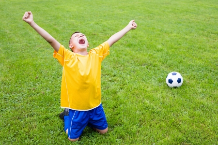 Excited boy football player after goal scored