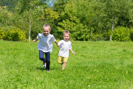 Happy joyful kids running on the grass in the autumn park