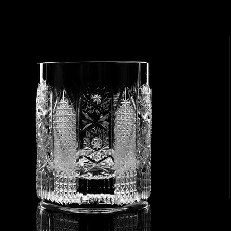 crystal whiskey glass reflected on black background