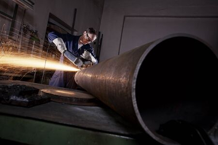 Photo pour Worker cutting pipe with angel grinder. - image libre de droit
