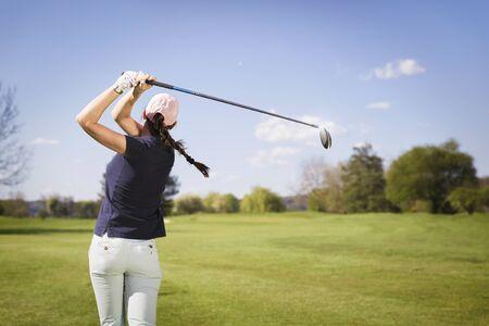 Photo pour Female golf player swinging golf club. - image libre de droit