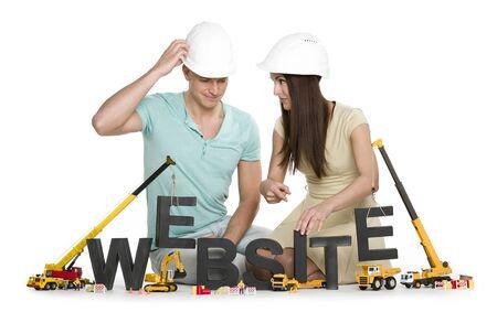 Photo pour Website under construction: Friendly man and woman building website-word. - image libre de droit