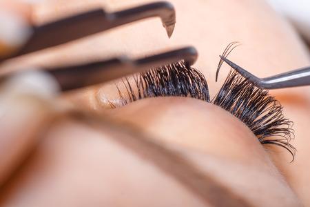 Photo pour Eyelash Extension Procedure. Woman Eye with Long Eyelashes. Lashes. Close up, macro, selective focus - image libre de droit