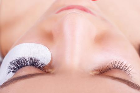 Photo pour Eyelash Extension Procedure. Woman Eye with Long Eyelashes. Lashes. Close up, selected focus. - image libre de droit