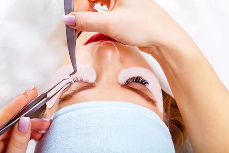 Foto de Eyelash Extension Procedure. Woman Eye with Long Eyelashes. Lashes. Close up, selected focus. - Imagen libre de derechos
