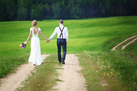 Back view of romantic couple of bride and groom walking hand in hand on rural road.の写真素材