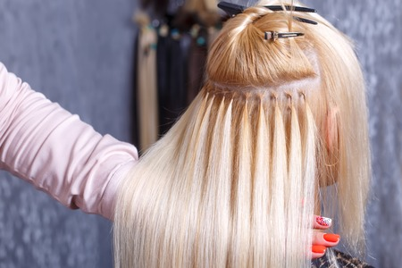 Photo for Hair extensions procedure. Hairdresser does hair extensions to young girl, blonde in a beauty salon. Selective focus. - Royalty Free Image