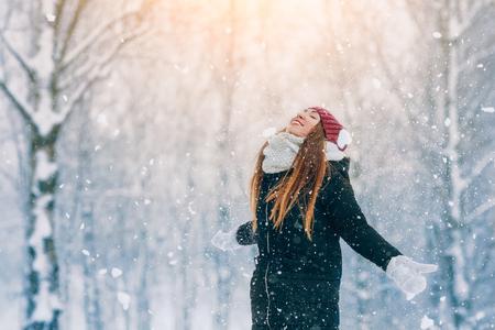 Winter young woman portrait. Beauty Joyful Model Girl laughing and having fun in winter park. Beautiful young woman outdoors. Enjoying nature, wintertime