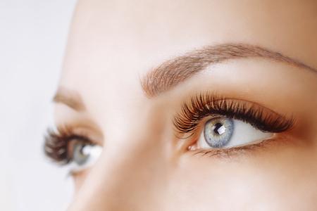 Photo pour Eyelash Extension Procedure. Woman Eye with Long Eyelashes. Close up, selective focus. - image libre de droit