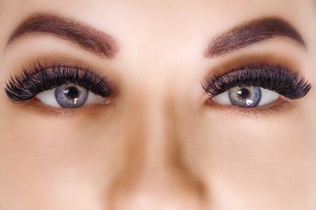 Photo pour Eyelash Extension Procedure. Woman Eye with Long Eyelashes. Close up, selective focus. Hollywood, russian volume - image libre de droit