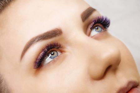 Photo pour Eyelash Extension Procedure. Woman Eye with Long Blue Eyelashes. Ombre effect. Close up, selective focus. - image libre de droit