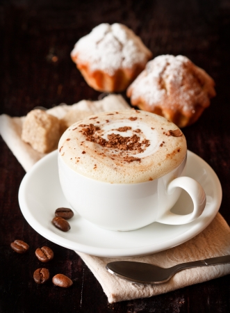Cup of coffee with chocolate, coffee beans and muffins on a dark background