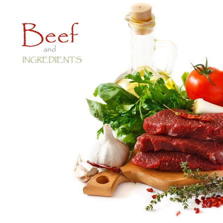 Raw beef meat with spices and herbs on a white background