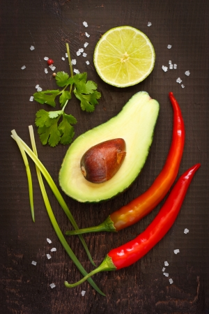 Ingredients for guacamole dip on a dark background