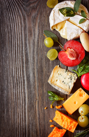 Assortment of delicious cheeses and fruit on a wooden background with copy space for text.