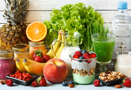 Healthy food concept. Fresh fruit and berries, granola and yogurt, smoothies and green wheat grass juice, almond milk and goji.の写真素材
