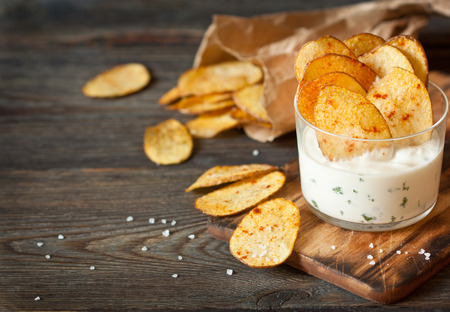 Homemade potato chips and spicy dip served in glass.