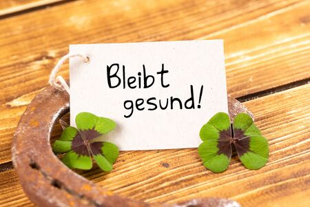 Photo for horseshoe with green shamrock sign for luck and german text bleibt gesund, in english stay healthy - Royalty Free Image