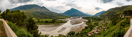 Stitched panorama of Mat river or Lumi, Albania, cloudy springtime day landscape with green foliage and beautiful mountains