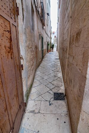 Very narrow street with limestone patio view with old building walls from the old town, Noci. Puglia. Italy, sunny and warm summer day