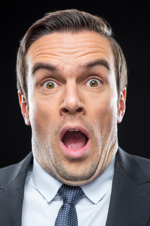 Close-up portrait of young scared businessman looking at camera